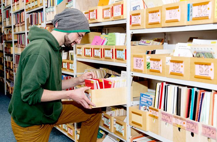 Bibliothek der TSB - Mitarbeiter an Regal