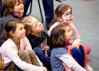 Kinder gucken lachend und interessiert beim Theater spielen zu